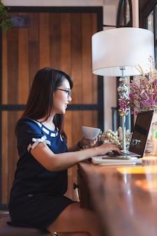 A fêmea asiática do negócio que trabalha com portátil faz uma anotação na cafetaria como o fundo.
