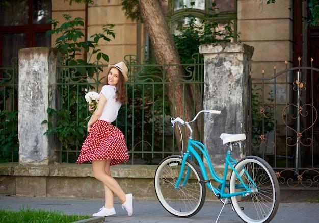 A fêmea bonita de sorriso prende flores e sorri para a câmera com a bicicleta azul do vintage perto dela que está na frente da casa velha bonita