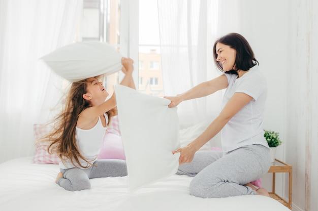 A fêmea de aparência agradável tem alegria junto com sua filha pequena, briga de travesseiros no quarto, pose na acolhedora e espaçosa sala de luz