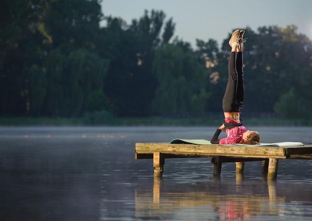 A fêmea está praticando ioga no lago. esporte e conceito lifestyle