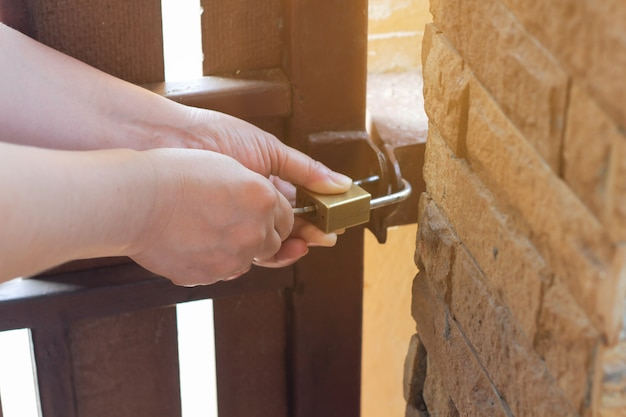 A fêmea gira a chave na fechadura da porta exterior aberta