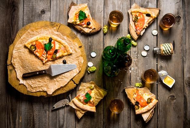 A festa da pizza. pizza e cerveja para quatro pessoas. em uma mesa de madeira. vista do topo