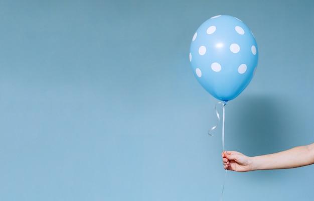 A festa de anos ou feriados à moda com balões fecha-se acima do retrato de estúdio. mão que mantém o balão colorido azul interno.
