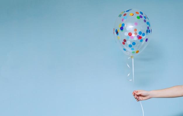 A festa de anos ou feriados à moda com balões fecha-se acima do retrato de estúdio. mão segurando o balão colorido interior.