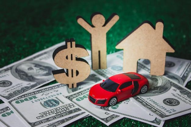 A figura de madeira com dinheiro do dólar, casa, carro assina dentro o negócio e o conceito financeiro.