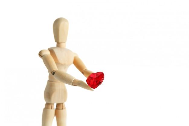 A figura de madeira de um homem tem nas mãos um coração vermelho sobre uma superfície branca, dá o coração