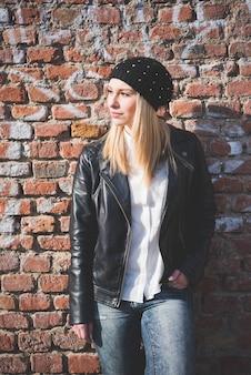 A figura do joelho da mulher loura bonita nova do cabelo reto na cidade que inclina-se em uma parede de tijolo, negligenciando à esquerda, pensativo - pensando o conceito futuro - vestindo a jaqueta de couro traseira, calças de brim, camisa branca