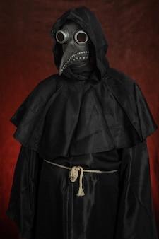 A figura negra de um homem com uma máscara de médico da peste fica sobre fundo vermelho