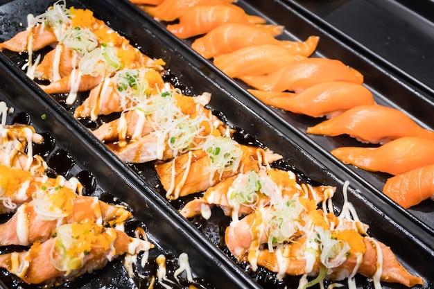 A fileira do sushi salmon serviu no prato preto no restaurante japonês.