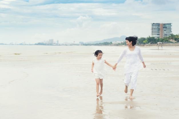 A filha asiática feliz da mãe e da criança da família corre, ri e joga na praia.