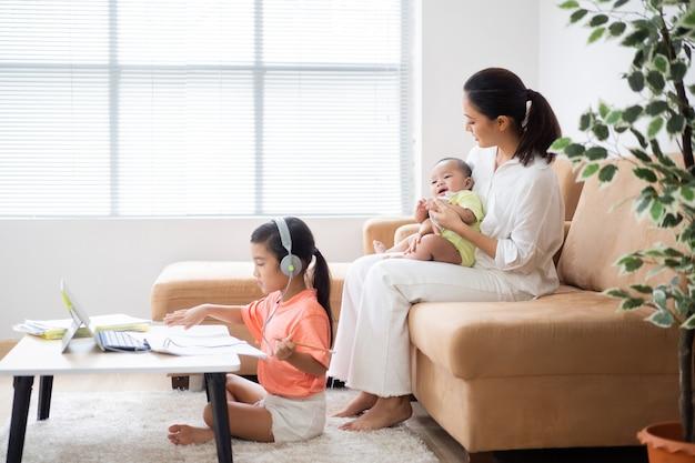 A filha dela está estudando online em casa. a mãe dela está com um bebê