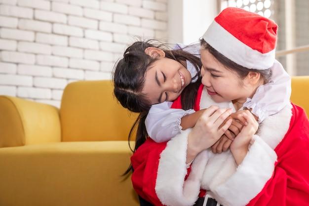 A filha do abraço da mãe em chapéus de santa comemora o natal em casa.