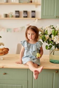 A filha do bebê na manhã toma o café da manhã na cozinha.