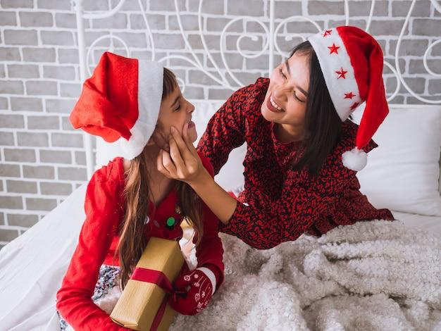 A filha e a mãe comemoram o dia de natal em casa
