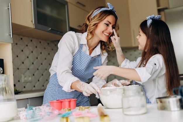 A filha e a mãe divertem-se durante o cozimento.
