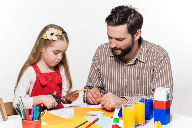 A filha e o pai fazendo aplicações de papel