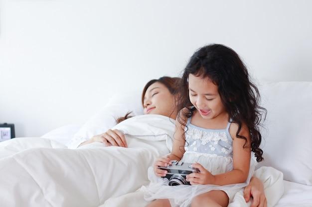A filha estava olhando para uma bela foto da câmera e a mãe dormindo na cama.
