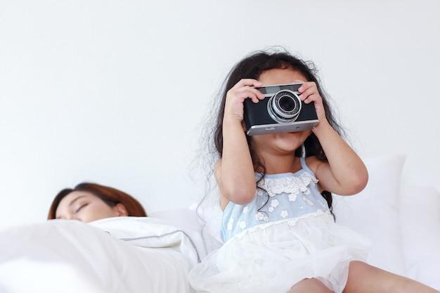 A filha estava tirando uma foto da câmera e a mãe dormindo na cama.