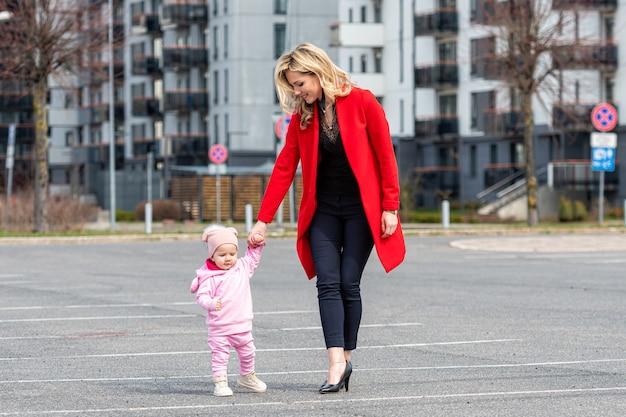 A filhinha anda de mãos dadas com a sua jovem mãe, a alegria de estarem juntos