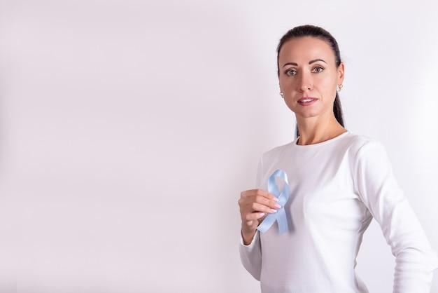 A fita azul em uma mão feminina simboliza a conscientização do câncer de próstata e a saúde masculina