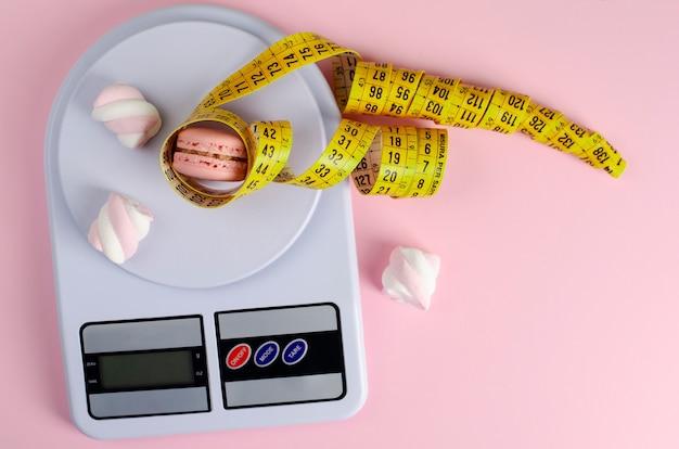 A fita de medição amarela, cozinha digital escala com macarons e marshmallows no rosa pastel.