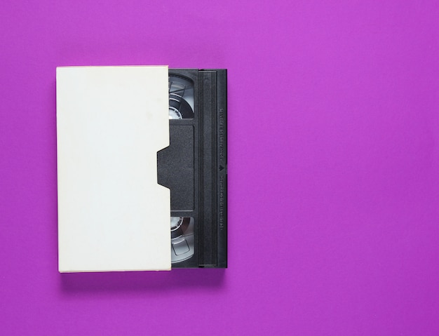 A fita de vídeo em um estojo de papel em um fundo roxo