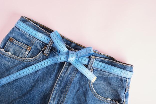 A fita métrica azul é enfiada em jeans em vez de um cinto, jeans azul em um fundo rosa