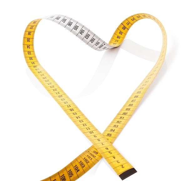 A fita métrica faz o coração em um fundo branco