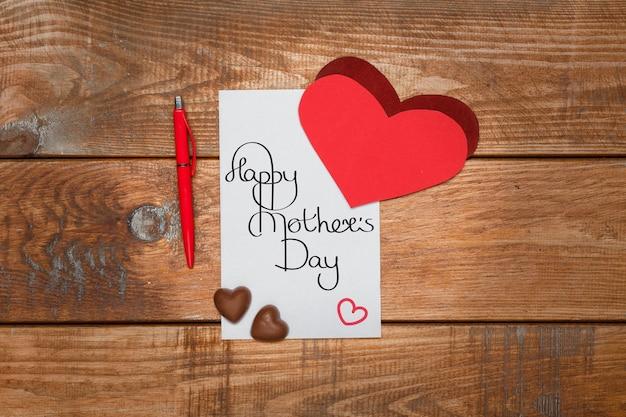 A fita vermelha, pequenos corações e uma folha de papel em branco e uma caneta sobre fundo de madeira. conceito de feliz dia das mães