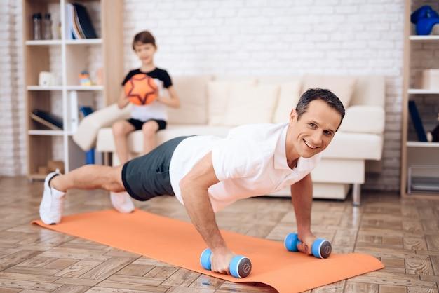 A flexão de homem, segurando um haltere. Foto Premium