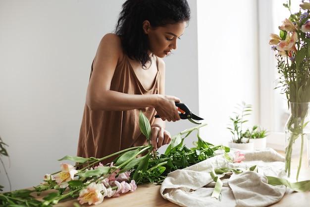 A flor de corte fêmea africana atrativa do florista decorre no local de trabalho.