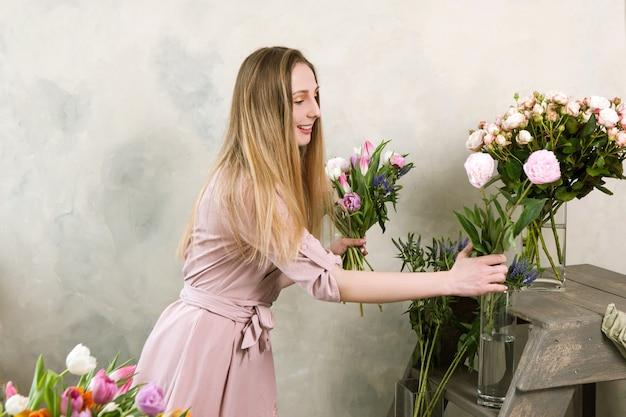 A florista escolhe uma flor para o buquê. oficina de decoradores. mulher no local de trabalho da floricultura, montando uma composição rosa primavera