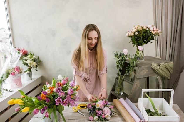 A florista na oficina embala um buquê. o decorador trabalha com sua criação. mulher em floricultura fazendo floricultura