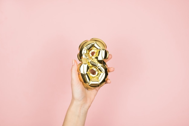 A folha de ouro balloons o numeral 8 na mão femine na superfície do rosa. feliz dia das mulheres