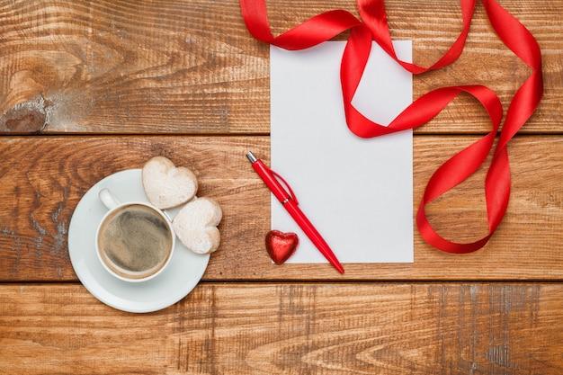 A folha de papel em branco e uma caneta com pequenos corações