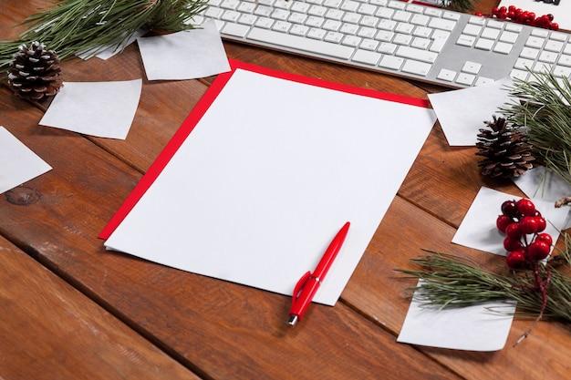 A folha de papel em branco na mesa de madeira com uma caneta e enfeites de natal. conceito de maquete de natal