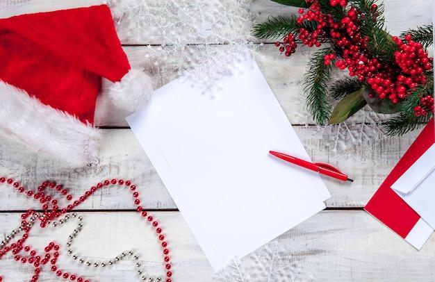 A folha de papel em branco na mesa de madeira com uma caneta e enfeites de natal.