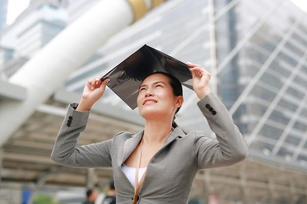 A folha de tampa aberta bonita da mulher de negócio e põe sobre sua cabeça para obstruir o sol.