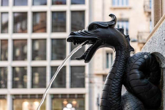 A fonte chamada escalade, bicos de água na fonte através do dragão de bronze, close-up, genebra, suíça