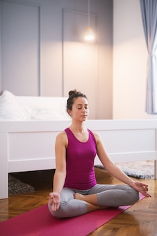 A forma atrativa desportiva meio envelheceu a mulher que faz poses assentados da ioga no assoalho antes de dormir.