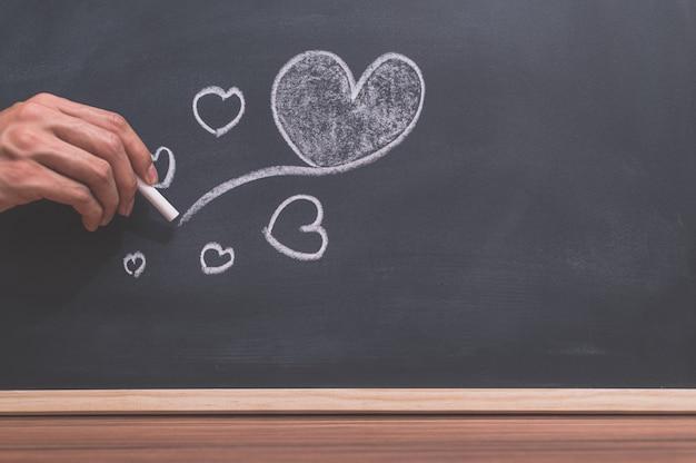 A forma de coração está no quadro negro, choque de escrita à mão.