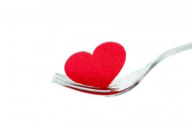 A forma de coração vermelho no garfo de prata, romance amor dinning ou conceito de cuidados de saúde coração