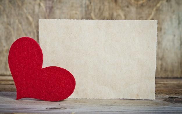 A forma de um cartão na mesa de madeira. o coração feito à mão de feltro vermelho está no canto esquerdo do formulário