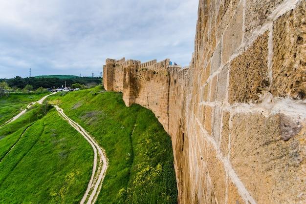 A forte parede de pedra de uma antiga fortaleza defensiva