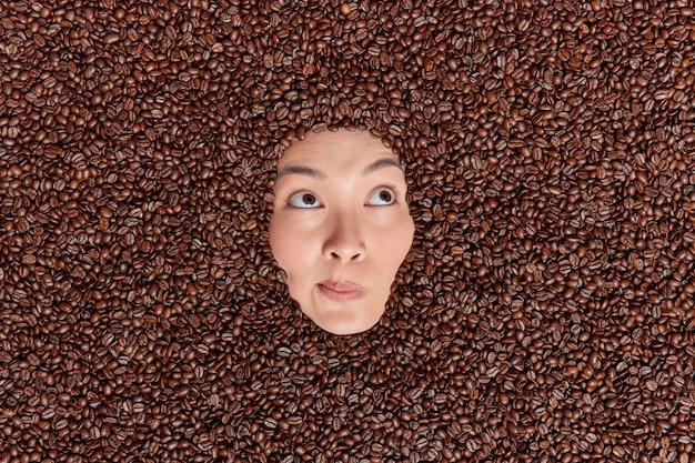 A foto aérea de uma mulher asiática mostra apenas o rosto através dos grãos de café que contêm muita cafeína, o que ajuda a melhorar a memória e a funcionalidade mental. modelo feminina em torno de uma guloseima saborosa