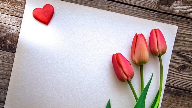 A foto com três tulipas vermelhas e coração vermelho em papel