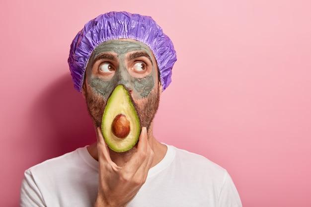 A foto da cabeça do homem em foco olha para cima, mantém a fatia de abacate perto do rosto, aplica máscara de argila, remove pontos pretos da pele