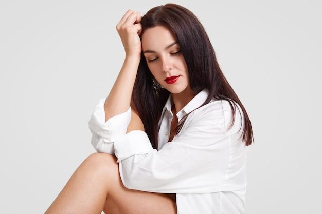 A foto da fêmea moreno de vista agradável com os lábios pintados vermelhos, cabelo escuro, pernas delgadas, inclina-se na mão, focalizada para baixo, levanta para a revista de moda, isolada no branco. mulher sexual elegante
