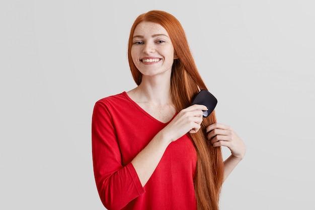 A foto da jovem mulher alegre gengibre sardenta sorridente penteia seus longos cabelos vermelhos, contente por se preparar para o encontro com o namorado, isolado sobre a parede branca. mulher se preocupa com o cabelo dela. conceito de beleza