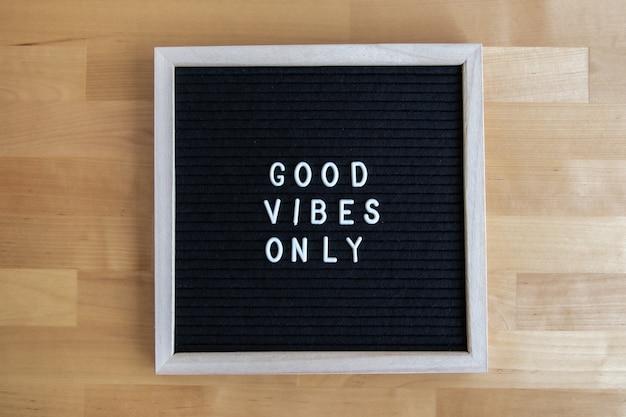 A foto da vista superior de um quadro-negro com boas vibrações, apenas uma citação sobre ele em uma mesa de madeira